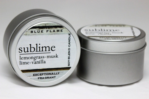 There are two silver, modern designed travel tins in the image. One tin is on it's side to show what the top of the label looks like on the lid: It says: sublime underlined in the middle of the label, and is off set towards the left side in large text, lemongrass-musk-lime-vanilla are written below in a smaller font. The Blue Flame logo is at the top of the label. Soy-blend Candle is written on the right side in a vertical line. On the bottom of the label is written, Exceptionally Fragrant. The other tin is flat and shows that the tin is just silver without a wrap around label. The modern design uses pale hues and simplistic lines.