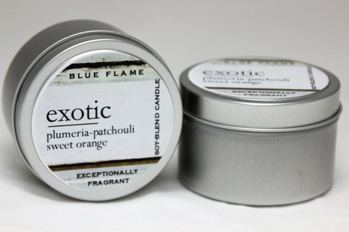 There are two silver, modern designed travel tins in the image. One tin is on it's side to show what the top of the label looks like on the lid: It says: exotic underlined in the middle of the label, and is off set towards the left side in large text, plumeria-patchouli-sweet orange are written below in a smaller font. The Blue Flame logo is at the top of the label. Soy-blend Candle is written on the right side in a vertical line. On the bottom of the label is written, Exceptionally Fragrant. The other tin is flat and shows that the tin is just silver without a wrap around label. The modern design uses pale hues and simplistic lines.