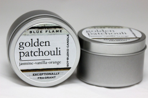 There are two silver, modern designed travel tins in the image. One tin is on it's side to show what the top of the label looks like on the lid: It says: golden patchouli underlined in the middle of the label, and is off set towards the left side in large text, jasmine-vanilla-orange are written below in a smaller font. The Blue Flame logo is at the top of the label. Soy-blend Candle is written on the right side in a vertical line. On the bottom of the label is written, Exceptionally Fragrant. The other tin is flat and shows that the tin is just silver without a wrap around label. The modern design uses pale hues and simplistic lines.