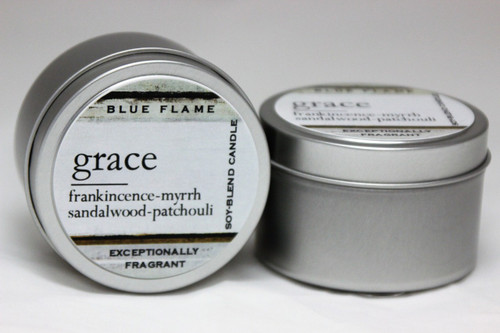 There are two silver, modern designed travel tins in the image. One tin is on it's side to show what the top of the label looks like on the lid: It says: grace underlined in the middle of the label, and is off set towards the left side in large text, frankincense-myrrh-sandalwood-patchouli are written below in a smaller font. The Blue Flame logo is at the top of the label. Soy-blend Candle is written on the right side in a vertical line. On the bottom of the label is written, Exceptionally Fragrant. The other tin is flat and shows that the tin is just silver without a wrap around label. The modern design uses pale hues and simplistic lines.