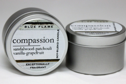 There are two silver, modern designed travel tins in the image. One tin is on it's side to show what the top of the label looks like on the lid: It says: compassion underlined in the middle of the label, and is off set towards the left side in large text, sandalwood-patchouli-vanilla-grapefruit are written below in a smaller font. The Blue Flame logo is at the top of the label. Soy-blend Candle is written on the right side in a vertical line. On the bottom of the label is written, Exceptionally Fragrant. The other tin is flat and shows that the tin is just silver without a wrap around label. The modern design uses pale hues and simplistic lines.