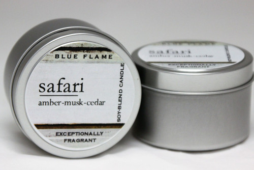 There are two silver, modern designed travel tins in the image. One tin is on it's side to show what the top of the label looks like on the lid: It says: safari underlined in the middle of the label, and is off set towards the left side in large text, amber-musk-cedar are written below in a smaller font. The Blue Flame logo is at the top of the label. Soy-blend Candle is written on the right side in a vertical line. On the bottom of the label is written, Exceptionally Fragrant. The other tin is flat and shows that the tin is just silver without a wrap around label. The modern design uses pale hues and simplistic lines.