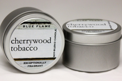 There are two silver, modern designed travel tins in the image. One tin is on it's side to show what the top of the label looks like on the lid: It says: cherrywood tobacco in the middle of the label, and is off set towards the left side in large text. The Blue Flame logo is at the top of the label. Soy-blend Candle is written on the right side in a vertical line. On the bottom of the label is written, Exceptionally Fragrant. The other tin is flat and shows that the tin is just silver without a wrap around label. The modern design uses pale hues and simplistic lines.