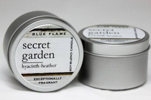 There are two silver, modern designed travel tins in the image. One tin is on it's side to show what the top of the label looks like on the lid: It says: secret garden underlined in the middle of the label, and is off set towards the left side in large text, hyacinth-heather are written below in a smaller font. The Blue Flame logo is at the top of the label. Soy-blend Candle is written on the right side in a vertical line. On the bottom of the label is written, Exceptionally Fragrant. The other tin is flat and shows that the tin is just silver without a wrap around label. The modern design uses pale hues and simplistic lines.