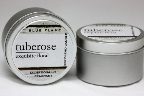 There are two silver, modern designed travel tins in the image. One tin is on it's side to show what the top of the label looks like on the lid: It says, tuberose underlined in the middle of the label, and is off set towards the left side in large text, exquisite floral is written below in a smaller font. The Blue Flame logo is at the top of the label. Soy-blend Candle is written on the right side in a vertical line. On the bottom of the label is written, Exceptionally Fragrant. The other tin is flat and shows that the tin is just silver without a wrap around label. The modern design uses pale hues and simplistic lines.