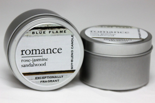There are two silver, modern designed travel tins in the image. One tin is on it's side to show what the top of the label looks like on the lid: It says, romance underlined in the middle of the label, and is off set towards the left side in large text, rose-jasmine-sandalwood are written below in a smaller font. The Blue Flame logo is at the top of the label. Soy-blend Candle is written on the right side in a vertical line. On the bottom of the label is written, Exceptionally Fragrant. The other tin is flat and shows that the tin is just silver without a wrap around label. The modern design uses pale hues and simplistic lines.