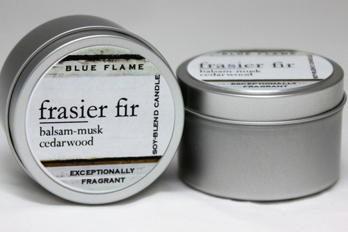 There are two silver, modern designed travel tins in the image. One tin is on it's side to show what the top of the label looks like on the lid: It says, frasier fir underlined in the middle of the label, and is off set towards the left side in large text, balsam-musk-cedarwood are written below in a smaller font. The Blue Flame logo is at the top of the label. Soy-blend Candle is written on the right side in a vertical line. On the bottom of the label is written, Exceptionally Fragrant. The other tin is flat and shows that the tin is just silver without a wrap around label. The modern design uses pale hues and simplistic lines.