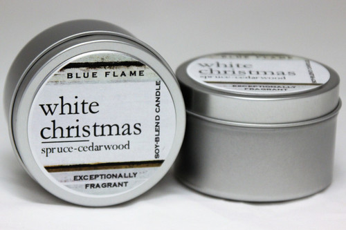 There are two silver, modern designed travel tins in the image. One tin is on it's side to show what the top of the label looks like on the lid: It says, white christmas underlined in the middle of the label, and is off set towards the left side in large text, spruce-cedarwood are written below in a smaller font. The Blue Flame logo is at the top of the label. Soy-blend Candle is written on the right side in a vertical line. On the bottom of the label is written, Exceptionally Fragrant. The other tin is flat and shows that the tin is just silver without a wrap around label. The modern design uses pale hues and simplistic lines.