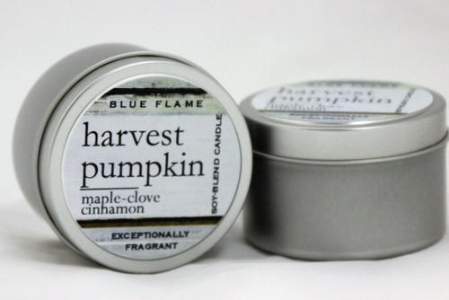 There are two silver, modern designed travel tins in the image. One tin is on it's side to show what the top of the label looks like on the lid: It says, harvest pumpkin underlined in the middle of the label, and is off set towards the left side in large text, maple-clove-cinnamon are written below in a smaller font. The Blue Flame logo is at the top of the label. Soy-blend Candle is written on the right side in a vertical line. On the bottom of the label is written, Exceptionally Fragrant. The other tin is flat and shows that the tin is just silver without a wrap around label. The modern design uses pale hues and simplistic lines.