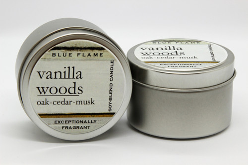 There are two silver, modern designed travel tins in the image. One tin is on it's side to show what the top of the label looks like on the lid: It says, vanilla woods underlined in the middle of the label, and is off set towards the left side in large text, oak-cedar-musk are written below in a smaller font. The Blue Flame logo is at the top of the label. Soy-blend Candle is written on the right side in a vertical line. On the bottom of the label is written, Exceptionally Fragrant. The other tin is flat and shows that the tin is just silver without a wrap around label. The modern design uses pale hues and simplistic lines.