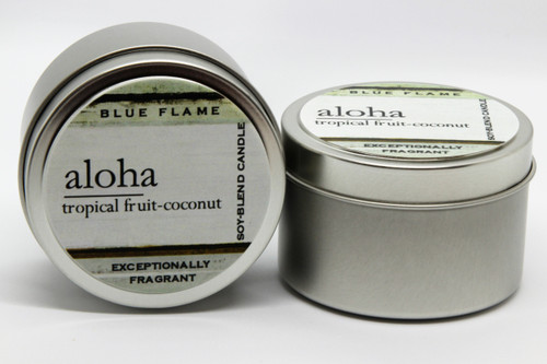 There are two silver, modern designed travel tins in the image. One tin is on it's side to show what the top of the label looks like on the lid: It says, aloha underlined in the middle of the label, and is off set towards the left side in large text, tropical fruit-coconut are written below in a smaller font. The Blue Flame logo is at the top of the label. Soy-blend Candle is written on the right side in a vertical line. On the bottom of the label is written, Exceptionally Fragrant. The other tin is flat and shows that the tin is just silver without a wrap around label. The modern design uses pale hues and simplistic lines.