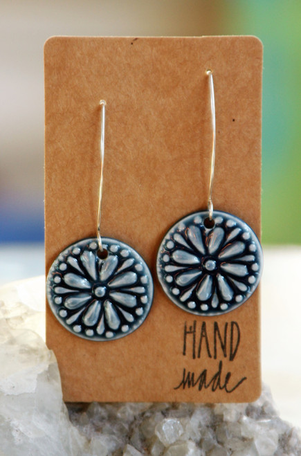 "Dark blue, flat porcelain flower design earrings that are about an inch in diameter and hang from a silver wire that is about 2 inches long. Earrings are presented on a light brown colored paper earring holder that is stamped with the words, ""Hand made."""