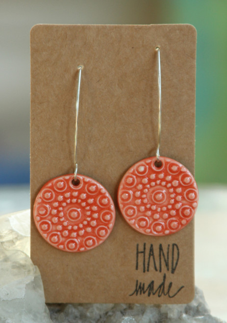 "Orange-red, flat porcelain flower design earrings that are about an inch in diameter and hang from a silver wire that is about 2 inches long. Earrings are presented on a light brown colored paper earring holder that is stamped with the words, ""Hand made."""