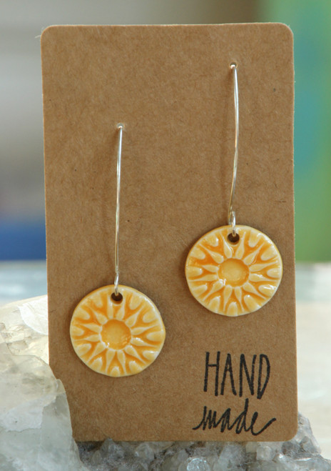 "Bright yellow,  flat porcelain sun design earrings that are about .75 inch in diameter and hang from a silver wire that is about 2 inches long. Earrings are presented on a light brown colored paper earring holder that is stamped with the words, ""Hand made."""