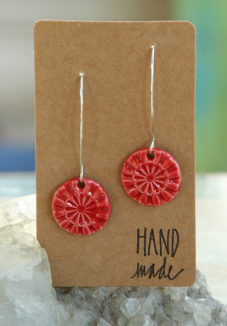 "Fire engine red,  flat porcelain flower design earrings that are about .75 inch in diameter and hang from a silver wire that is about 2 inches long. Earrings are presented on a light brown colored paper earring holder that is stamped with the words, ""Hand made."""