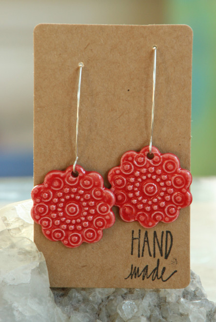 "Fire engine red, flat porcelain flower design earrings that are about an inch in diameter and hang from a silver wire that is about 2 inches long. Earrings are presented on a light brown colored paper earring holder that is stamped with the words, ""Hand made."""