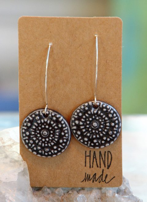 "Black, flat porcelain flower design earrings that are about an inch in diameter and hang from a silver wire that is about 2 inches long. Earrings are presented on a light brown colored paper earring holder that is stamped with the words, ""Hand made."""