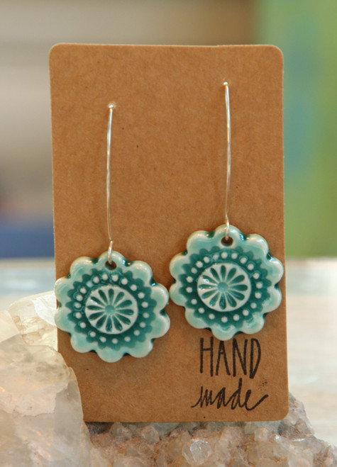 "Teal green, flat porcelain flower design earrings that are about an inch in diameter and hang from a silver wire that is about 2 inches long. Earrings are presented on a light brown colored paper earring holder that is stamped with the words, ""Hand made."""
