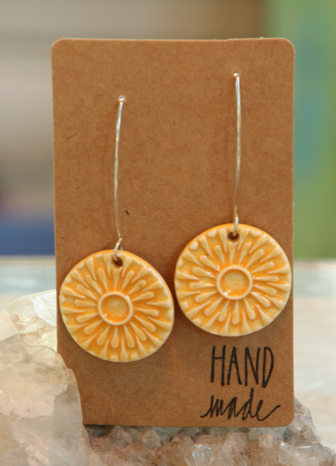 """Bright yellow,  flat porcelain sun design earrings that are about an inch in diameter and hang from a silver wire that is about 2 inches long. Earrings are presented on a light brown colored paper earring holder that is stamped with the words, """"Hand made."""""""