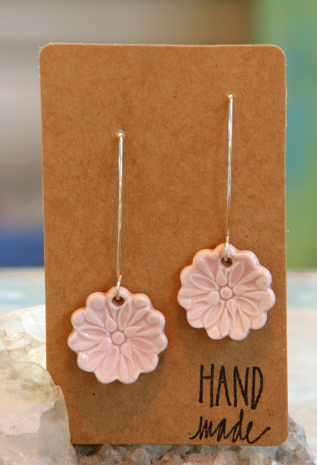"Pale pink,  flat porcelain flower design earrings that are about .75 inch in diameter and hang from a silver wire that is about 2 inches long. Earrings are presented on a light brown colored paper earring holder that is stamped with the words, ""Hand made."""