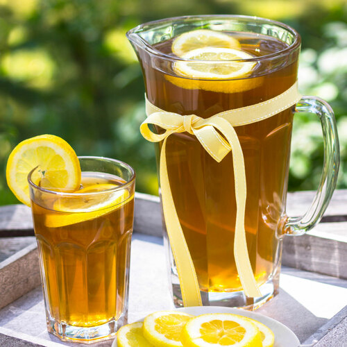 glass of iced tea with pitcher and lemons
