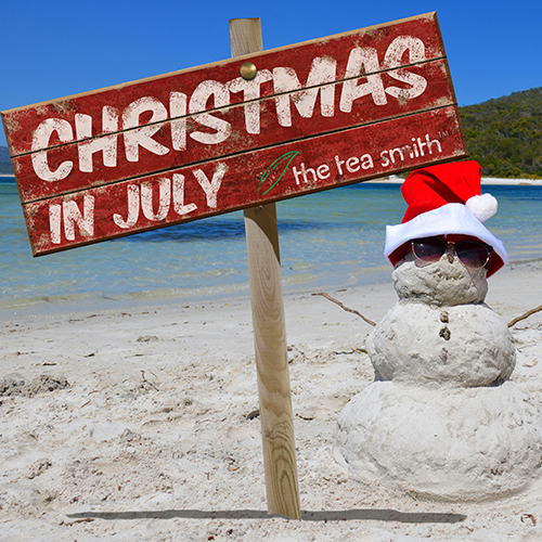 sign on beach with snowman made of sand