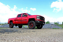 7in GM Suspension Lift | Strut Spacers (14-18 1500 PU 4WD | Stamped Steel) - passenger side view on red truck