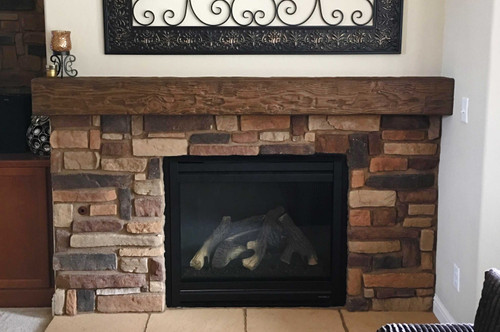 Our Tuscany Faux Wood mantel in the walnut color used to decorate a fireplace.