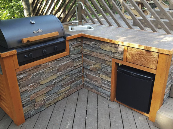 This backyard island with a grill paneled with our Dakota Dry Stack Wall panel in our earth color.