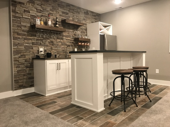Our Kentucky Dry Stack Stone Wall panels in the mist color are used as a backsplash for this beautiful home bar.