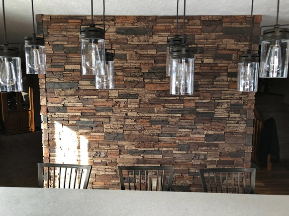 Dining room wall paneled with our Kentucky Dry Stack Stone Wall panels paired with their matching outside corners.