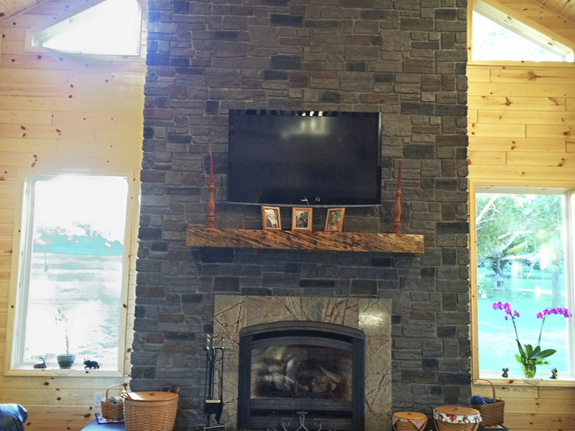 Fireplace decorated with our Lehigh Cobblestone Stone Wall panels in the smoke color.