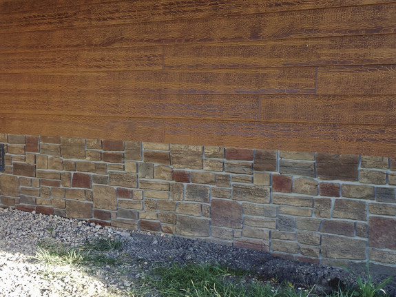 Our Lehigh Cobblestone Stone Wall panels in the harvest color used as skirting for this home.