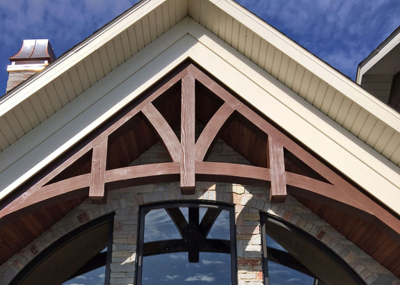 Our Woodland Faux Wood beam in the cedar color used as an outdoor decorative truss to the front of this home.