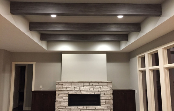 Living room ceiling decorated with our Resawn Faux Wood beams in the gray patina color.