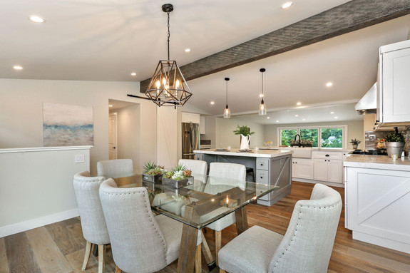 Our Reclaimed Faux Wood beam in the relic color used on the ceiling of this open-plan dining room and kitchen.
