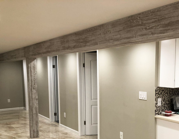 Hallway ceiling and column post decorated by our Driftwood Faux Wood beams in the whitewash color.