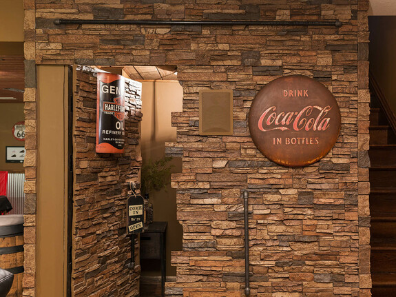 Basement hidden door paneled with our Colorado Dry Stack Stone Wall faux panels in the sierra brown color.