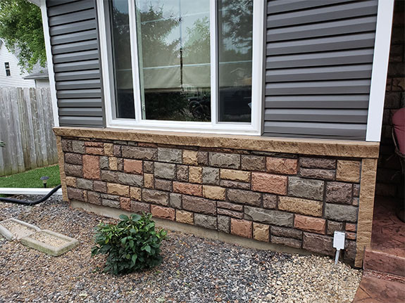 Front of a house paneled with our Regal Chiseled Stone panels/outside corners in the earth color.