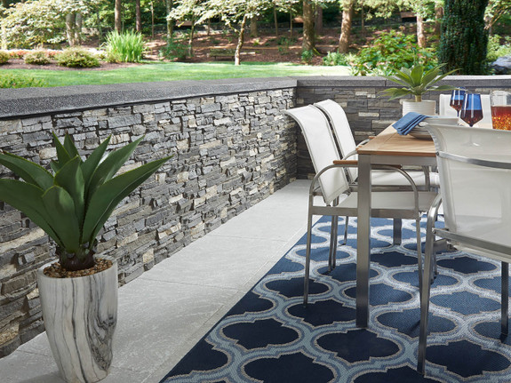 Colorado Dry Stack Stone Wall Panels in Iced Coffee used on an outdoor patio setting.