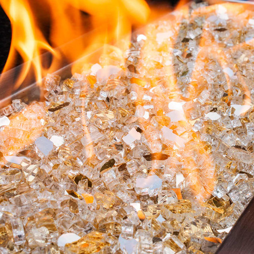 Close up of glimmering golden tempered fire glass in a large gas fire pit.