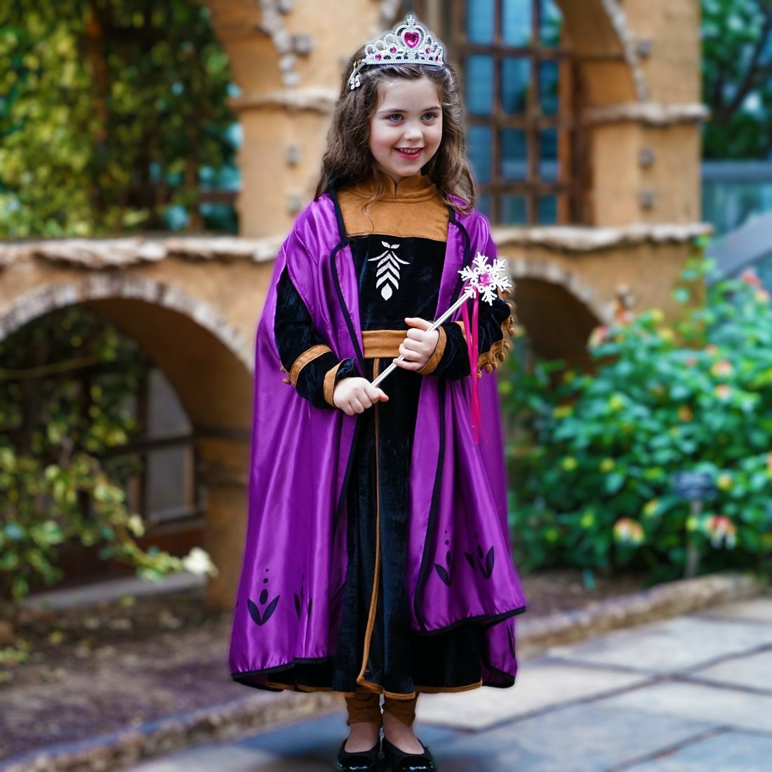 Little girl in a princess costume with a purple cape