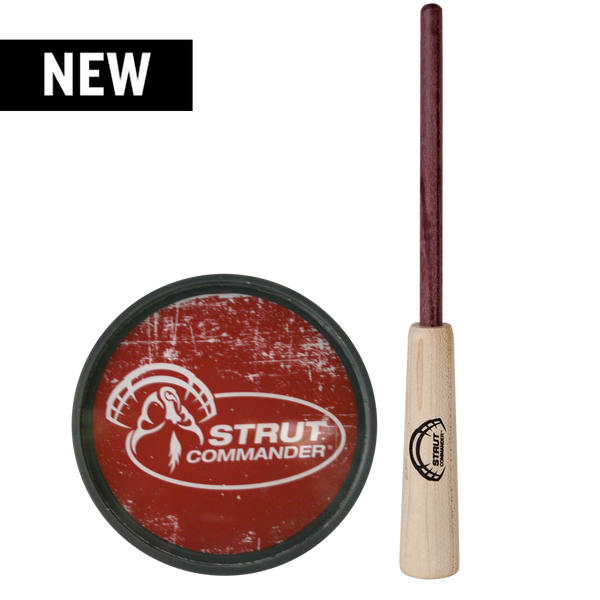 grey, polycarbonate base pot call with glass top that feature the full Strut Commander logo in white on top of a red, distressed background. Purple Heart wood striker.