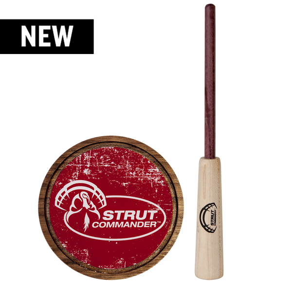 Walnut base pot call with a crystal surface featuring the full Strut Commander logo in white on top of a red, distressed background. Purple Heart wood striker.