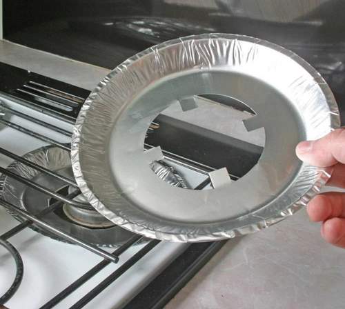 4pk STOVE BURNER LINERS (CAMCO) (07-1014) PICTURED BEING HELD OVER STOVE-TOP