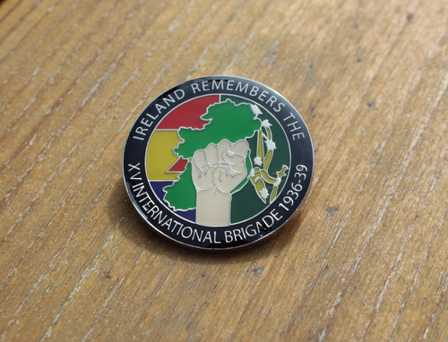 Badge has a map of Ireland, clenched fist, the Spanish Republican and Starry Plough flags and the text IRELAND REMEMBERS THE XV INTERNATIONAL BRIGADE 1936-39