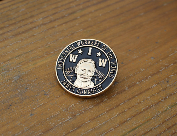 This badge has a 3D image of James Connolly on the background of the Industrial Workers of the World (IWW) logo.