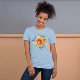 """Front view of light blue """"Watch Yourself Bloom"""" Relaxed Fit T-Shirt with pink and yellow bi-color rose and black text"""