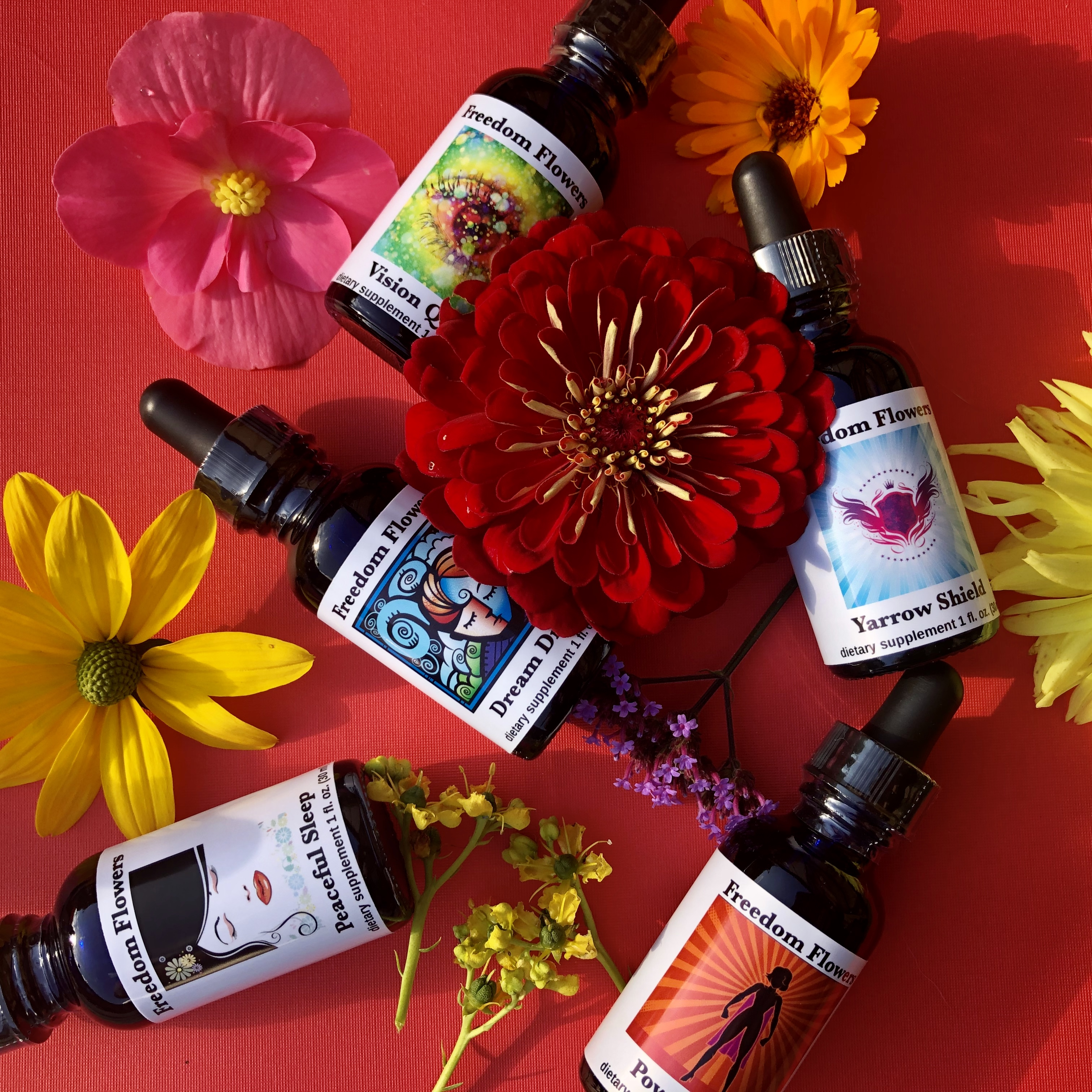 Bottles of flower essence blends with flowers strewn on red background