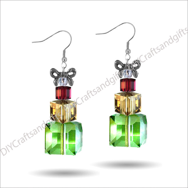 Beautiful Handmade Swarovski Crystal Earrings. The perfect gift for Christmas! Choose between Silver Plated, Gold Plated, Sterling Silver and 9ct Yellow Gold findings. These presents have Bow on the top (gold or silver - matching the findings), a Crystal bicone, small Siam (red) present, medium Gold present, and a large Peridot (green) present. Approx. 27mm long & 19mm wide at top of bow.